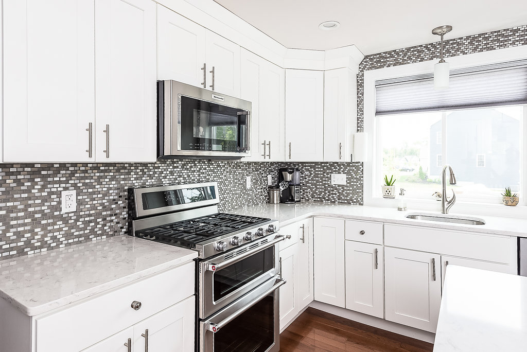 White kitchen with glass tile and stainless appliances